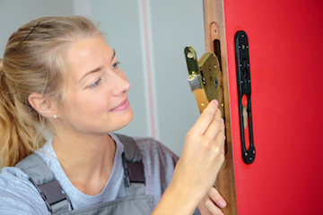 Lady locksmith fitting a lock to a door